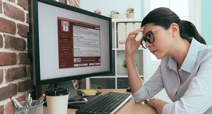 Female teacher researching K-12 cybersecurity threats schools are facing.