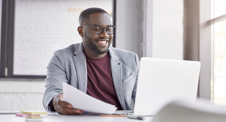 Male employee taking online marketing courses on his laptop to boost his business.