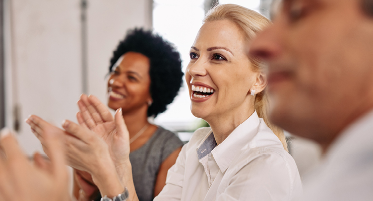 Employees satisfied with their job and smiling at a meeting.