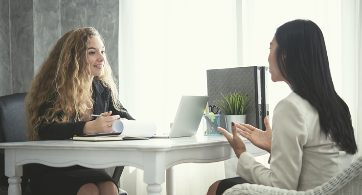 Female talking with a female coworker whether or not a career path in Human Resources is right for her or not.