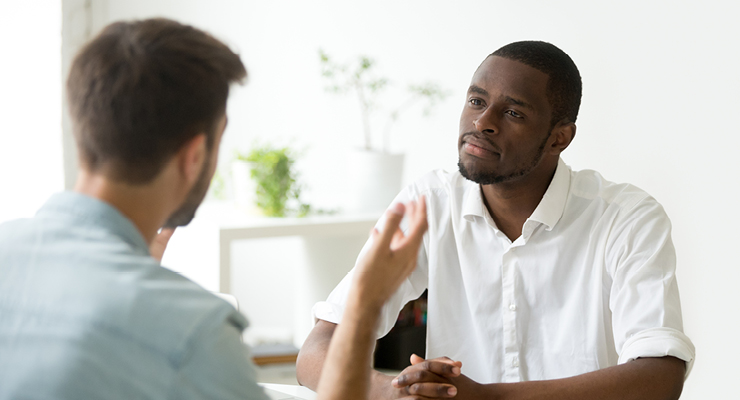 Male discussing with a male friend whether whether or not a Human Resources career path is right for him.