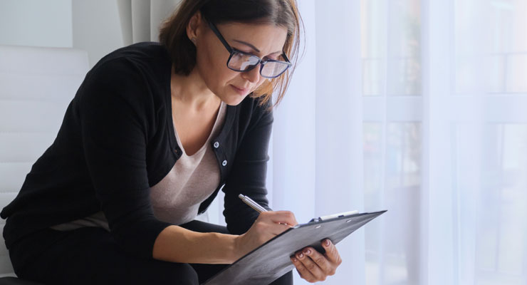 A woman takes notes at home