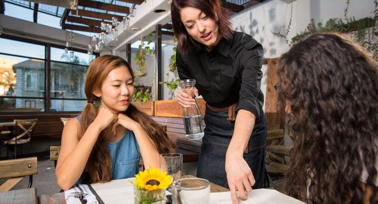 waitress helping customer read the menu