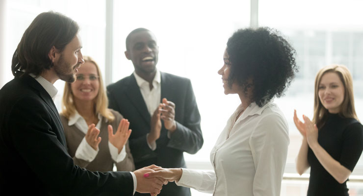 business manager recognizing and congratulating an employee in front of her colleagues