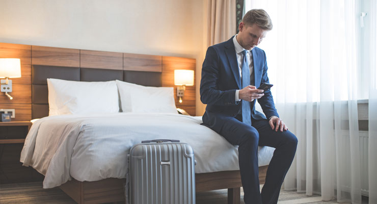 business man wearing suit sitting on edge of hotel bed