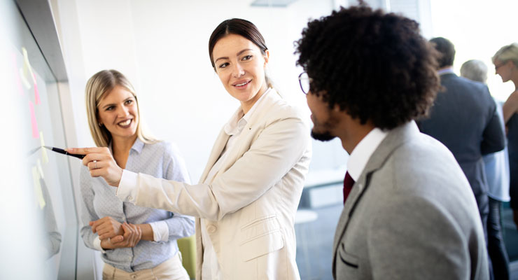 coworkers standing at drawing board and effectively communicating with one another