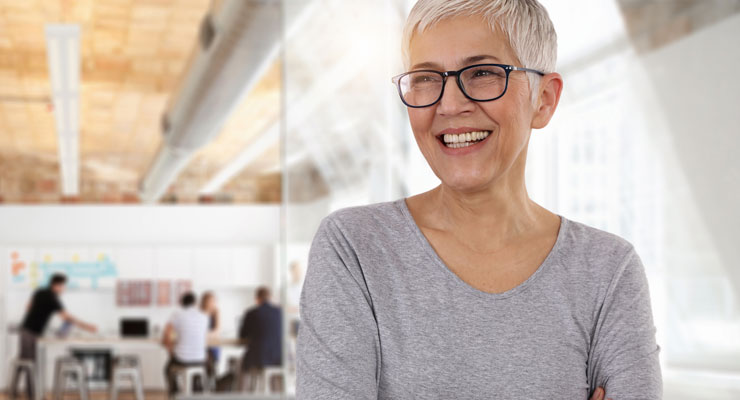 smiling woman with positive attitude in an open office workspace