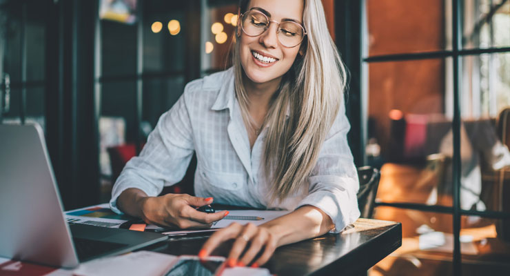 young professional woman in a cafe using social media to evaluate potential employers