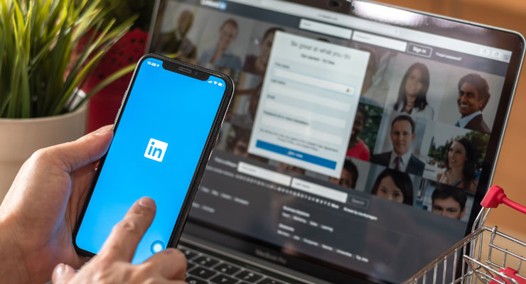 a professional using linkedin app on a phone in front of a laptop with linkedin