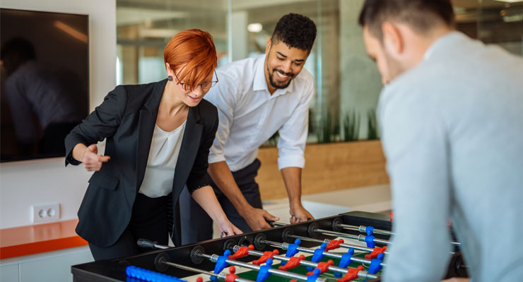 coworkers playing fussball in a corporate office