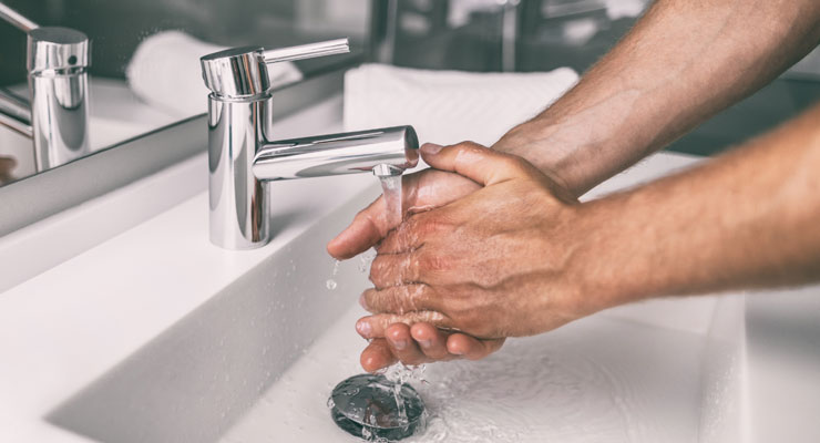 man washing his hands at the sink to prevent illness
