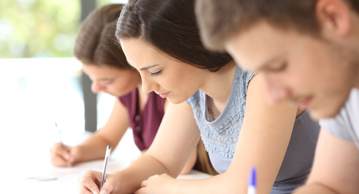 Three high school students with their heads down taking a test in class