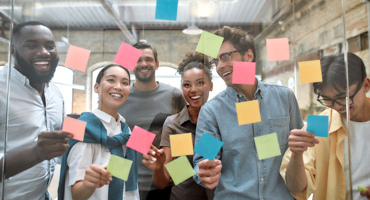 team of professionals laughing and having fun creating ideas together in front of a clear board with sticky notes