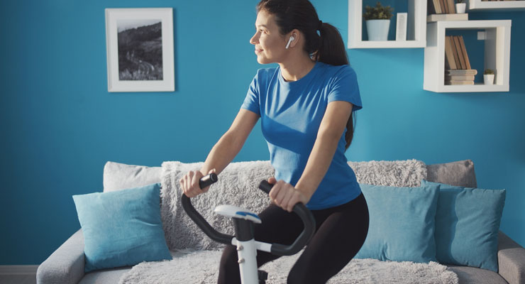 woman working from home and taking a break to exercise on stationary bike