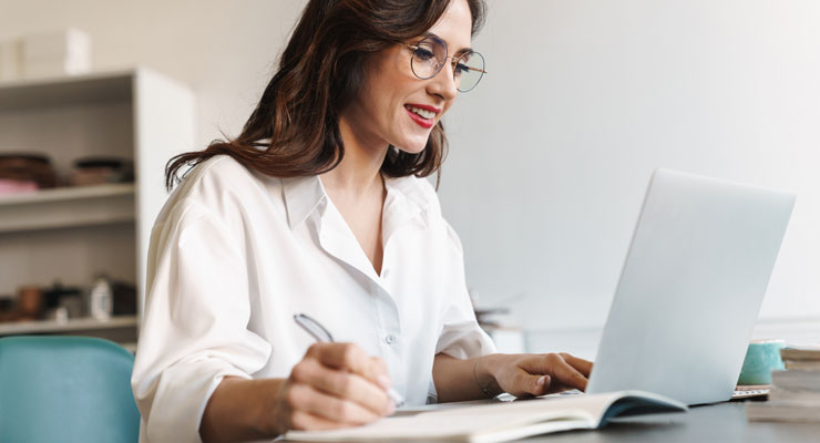 woman sitting at a desk looking at a laptop and jotting notes in a notebook