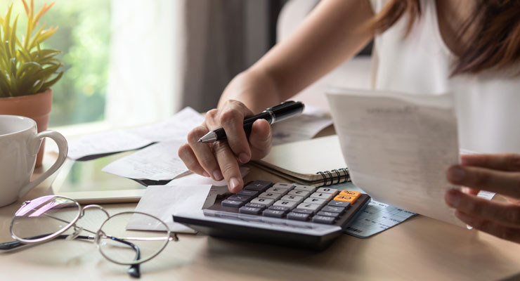 woman sitting at a table with paperwork and using a calculator to plan a budget
