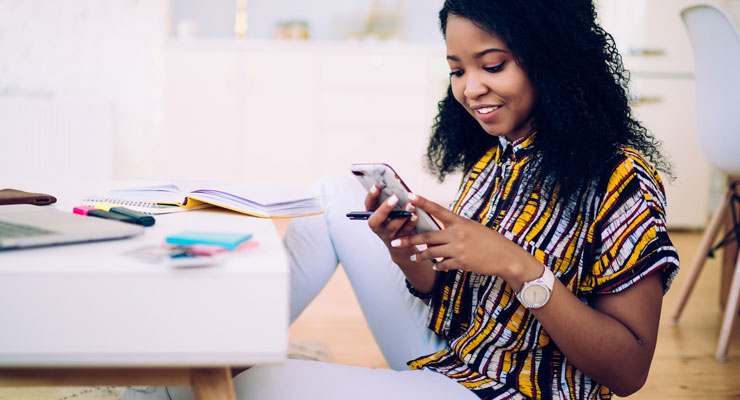 young woman sitting at a table with study materials. she is using an LSAT study app on her phone to study.