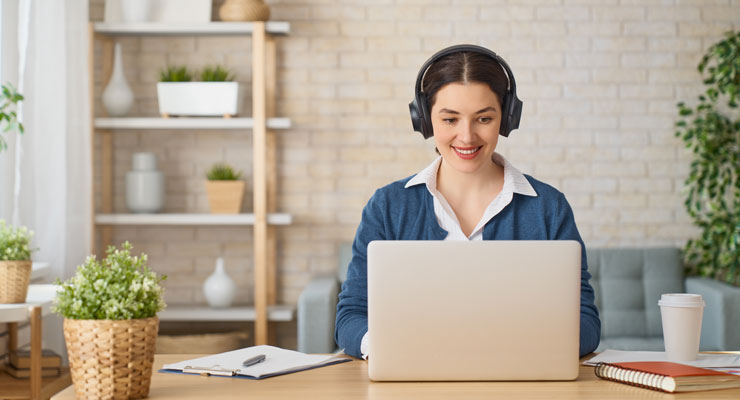 female-employee-working-productively-on-a-laptop-while-listening-to-music