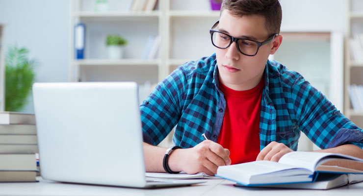 male student taking their SAT online at home on a laptop