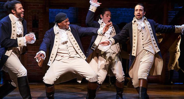 Three male actors performing the Hamilton play.
