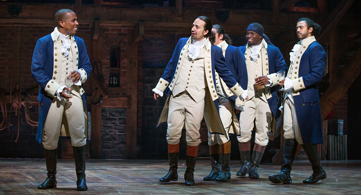 Group of male actors in the Hamilton play portraying a scene about sharing your ideas which ties into professional development.