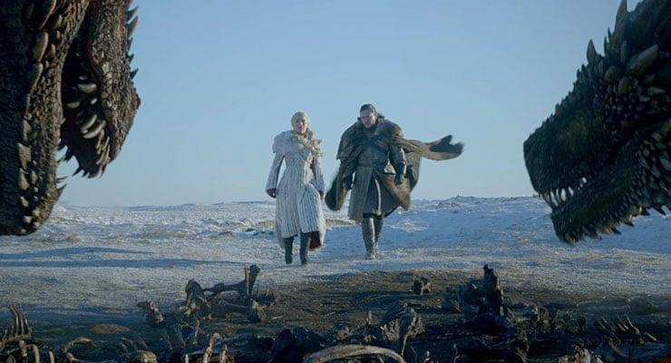Daenerys Targaryen and Jon Snow walking towards two dragons together