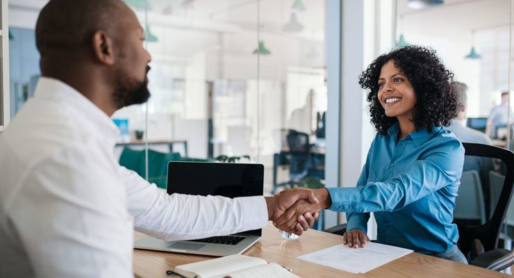 A male supervisor shakes hands with his female employee as they both smile