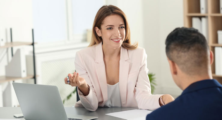 A man and a smiling woman have a conversation in an office at work