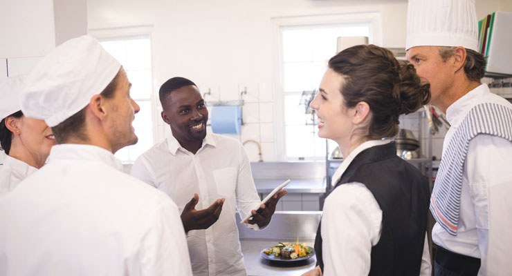 A hospitality manager laughs with kitchen staff before their shift begins