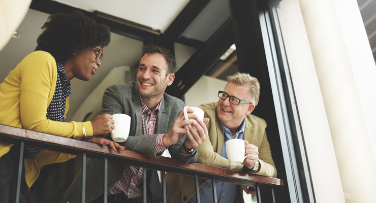 Three coworkers take a break from work to drink coffee and talk