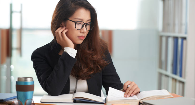 A paralegal student studies her legal assistant course material