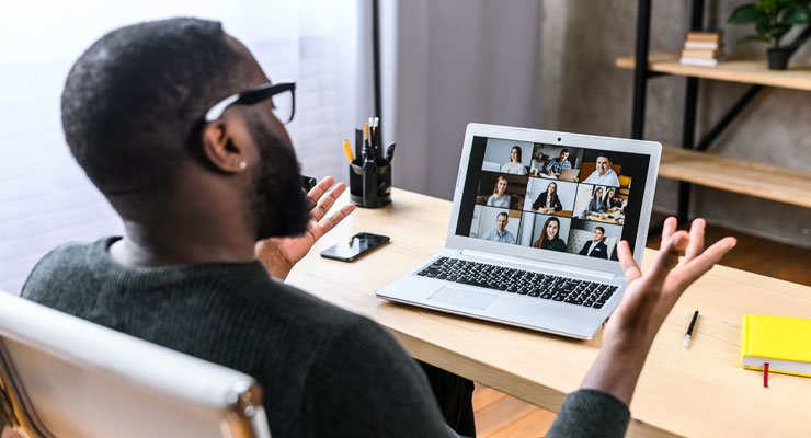 Male employee in a virtual team meeting working from home.